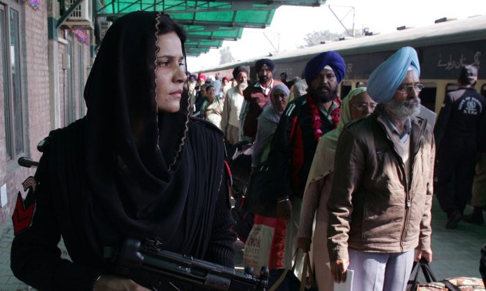 A Pakistani female police commando stands guard, as Indian Sikh pilgrims arrive at Wagah railway station near Lahore, Pakistan, on Nov. 20, 2015. Hundreds of Indian Sikh pilgrims arrived in Pakistan by a special train to participate in three-day festival to celebrate the 547st birth anniversary of their spiritual leader Baba Guru Nanak, the founder of Sikh religion, at Nankana Sahib near Lahore. (AP Photo/K.M. Chaudary)