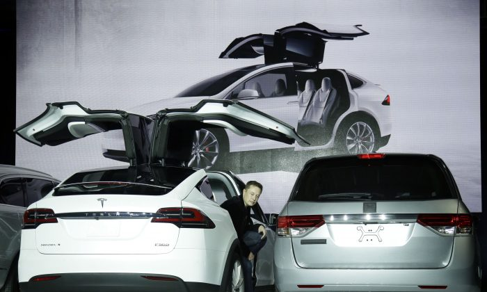 Elon Musk, CEO of Tesla Motors Inc., introduces the Model X car at the company's headquarters  in Fremont, Calif., Sept. 29, 2015. Tesla faces shareholder lawsuits that may delay its proposed merger with SolarCity. (AP Photo/Marcio Jose Sanchez)