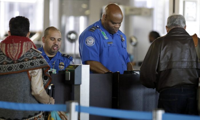 FILE - In this Nov. 25, 2015 file photo, Transportation Security Administration agents check travelers identifications at a security check point area in Terminal 3 at O'Hare International Airport in Chicago. (AP Photo/Nam Y. Huh, File)