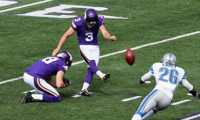Jeff Locke #18 of the Minnesota Vikings holds the ball as teammate Blair Walsh #3 kicks the extra point against Don Carey #26 of the Detroit Lions during the first quarter of the game on September 20, 2015 at TCF Bank Stadium in Minneapolis, Minnesota. (Photo by Hannah Foslien/Getty Images)
