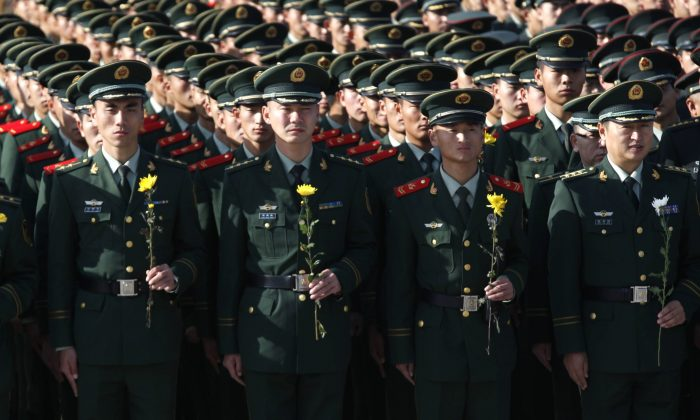 Chinese paramilitary soldiers hold flowers as they commemorate Martyrs' day in Heihe, northeast China's Heilongjiang province on September 30, 2015. CHINA OUT   AFP PHOTO        (Photo credit should read STR/AFP/Getty Images)