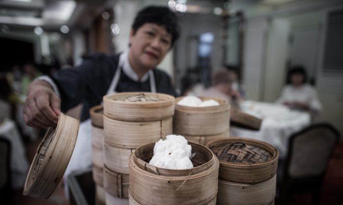 """A waitress serves baskets of dim sum on a trolley in a restaurant in Hong Kong.  With much of the city's famous """"dim sum"""" snacks now factory-made, a core of dedicated chefs are determined to prevent the handmade tradition from dying out.  (PHILIPPE LOPEZ/AFP/Getty Images)"""