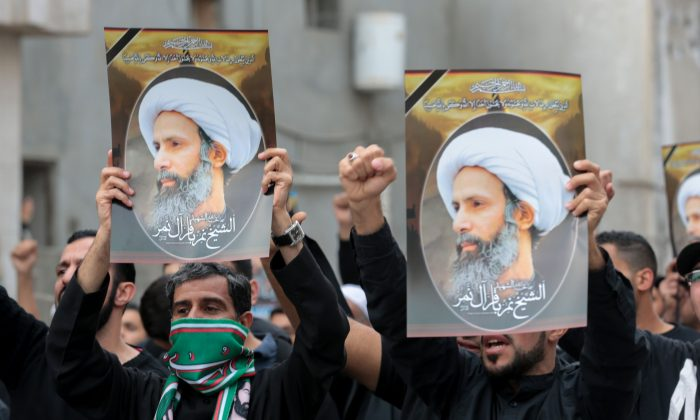 Saudi Shiite men hold placards bearing portraits of Shiite cleric Nimr al-Nimr during a protest on Jan. 8, 2016, in the eastern coastal city of Qatif, against his execution by Saudi authorities in Jan. 2. Nimr was a driving force of the protests that broke out in 2011 in the kingdom's Saudi Eastern Province, an oil-rich region where the Shiite minority of an estimated 2 million people complains of marginalization. (STR/AFP/Getty Images)