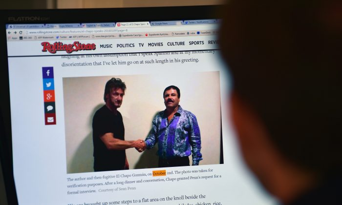 """A man reads an article about drug lord Joaquin Guzman, aka """"El Chapo,"""" showing a picture of him (R) and American actor Sean Penn on the website of Rolling Stone magazine, in Mexico City, on Jan. 10, 2016. (Alfredo Estrella/AFP/Getty Images)"""
