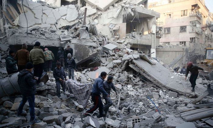 Syrians and civil defense workers evacuate victims from the rubble of a destroyed building following air strikes on the Eastern Ghouta town of Douma, a rebel stronghold east of the capital Damascus, on Jan. 10. (SAMEER AL-DOUMY/AFP/Getty Images)
