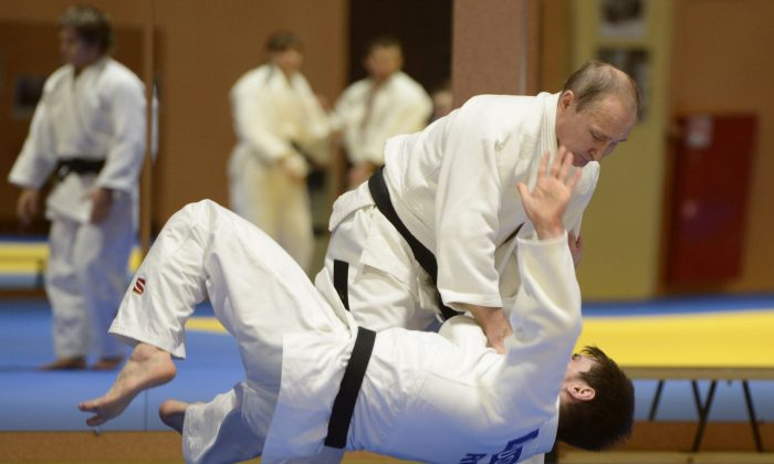 Russian President Vladimir Putin, top, competes against Musa Mogushkov, member of Russia Judo team during their training session in the resort city of Sochi, Russia, Friday, Jan. 8, 2016. After Russian President Vladimir Putin and national judo team coach Ezio Gamba took each other to the mat in a practice, Putin followed up with a smooth move, granting the Italian a Russian passport. (Alexei Nikolsky, Sputnik, Kremlin Pool Photo via AP)