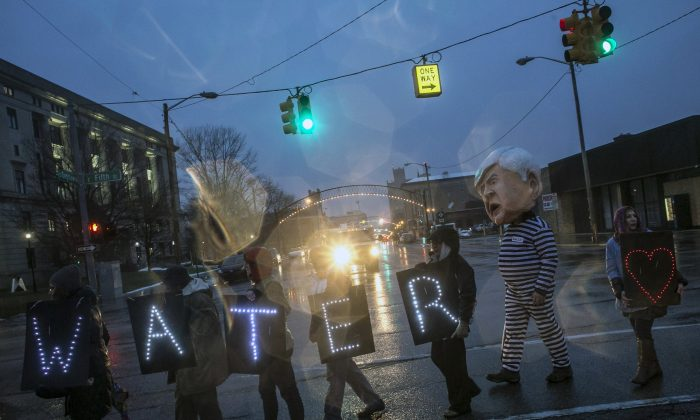 More than 150 protestors, including Bruce Fealk, of Rochester Hills, second from right, stand outside of Flint's City Hall to protest Michigan Gov. Rick Snyder's handling of the water crisis in downtown Flint, Mich., Friday, Jan. 8, 2016. (Sean Proctor/The Flint Journal-MLive.com via AP)
