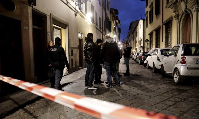 CORRECTS LAST NAME FROM OSLEN TO OLSEN- Italian police officers stand outside an apartment where 35-year-old American woman Ashley Olsen was found dead, in Florence, Italy, Saturday, Jan. 9, 2016. Italian police say the woman has been found slain in her apartment with bruises and scratches on her neck, but wouldn't comment on Italian news reports that the woman had been strangled until an autopsy is performed. (Maurizio Degl'Innocenti/ANSA via AP