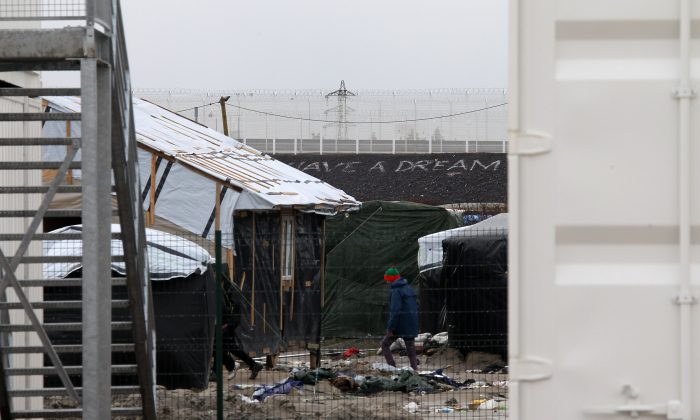 A migrant walks at the entrance of the Calais refugee camp in Calais, northern France, on Jan. 11, 2016. Approximately 130 containers will be converted to shelters to accommodate as many as 1,500 migrants who are expected to move in on Monday. (AP Photo/Michel Spingler)