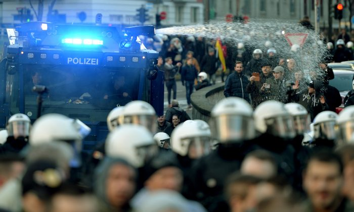 Police  drive back right-wing demonstrators using a water cannon during protests in Cologne, Germany, Saturday Jan. 9, 2016. (Monika Skolimowska/dpa via AP)