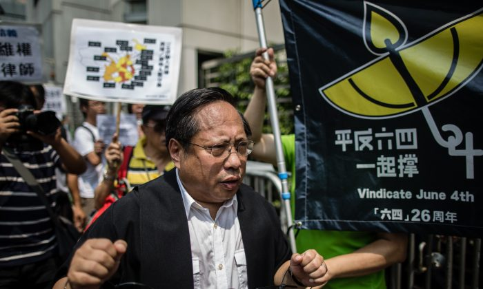 "Hong Kong Democratic Party's Albert Ho (C) wears mock handcuffs as he attends a protest in Hong Kong on July 12, 2015, after at least 50 Chinese human rights lawyers and activists were detained or questioned in recent days in an ""unprecedented"" police swoop, rights groups said on July 11, with around 20 still feared to be held. The scale of the clampdown on the legal profession began to emerge when a friend of lawyers and staff at a single Beijing law firm known for its human rights casework said at least five had been detained in the last couple of days. (Anthony Wallace/AFP/Getty Images)"