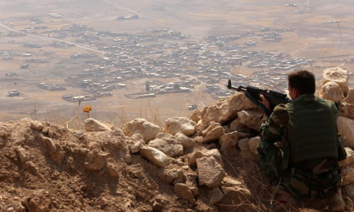 An Iraqi Kurdish Peshmerga fighter monitors his surrounding from the top of Mount Zardak, about 25 kilometers (15.5 miles) east of Mosul, on Aug. 6, 2015. (Safi Hamed/AFP/Getty Images)
