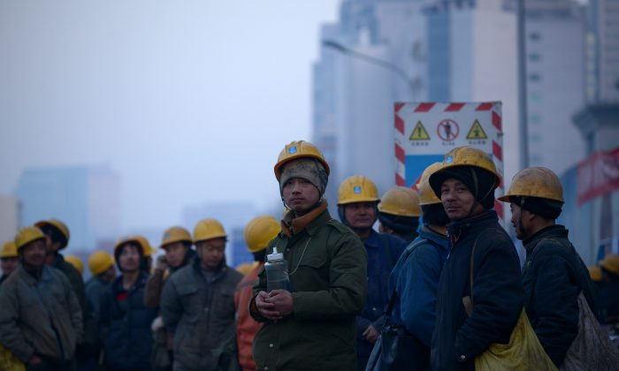 A group of workers wait outside of a construction site in Beijing Dec. 28, 2015. (Wang Zhao/AFP/Getty Images)