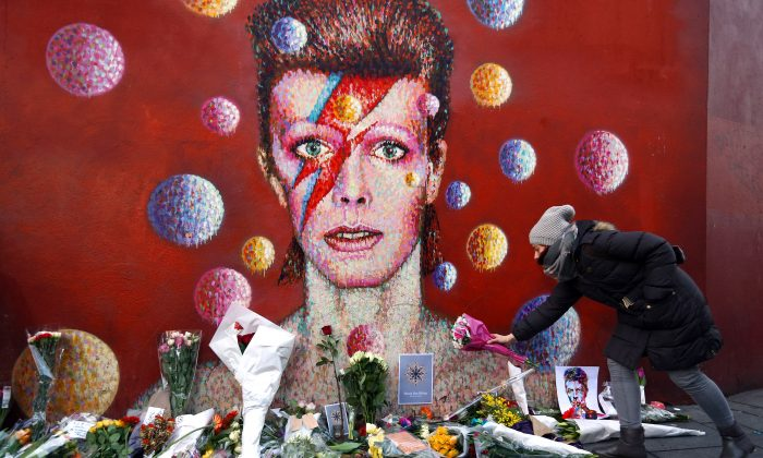 A woman leaves flowers beneath a mural of David Bowie in London on January 11, 2016. British music and fashion icon David Bowie died at the age of 69 after a battle with cancer. (Photo by Carl Court/Getty Images)