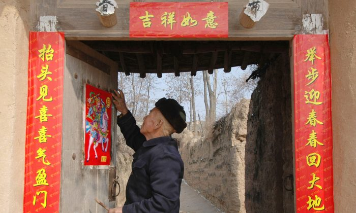 An elderly man pastes spring couplets on his door at a village on in Fu County of Shaanxi Province on Feb. 7, 2005. (China Photos/Getty Image)