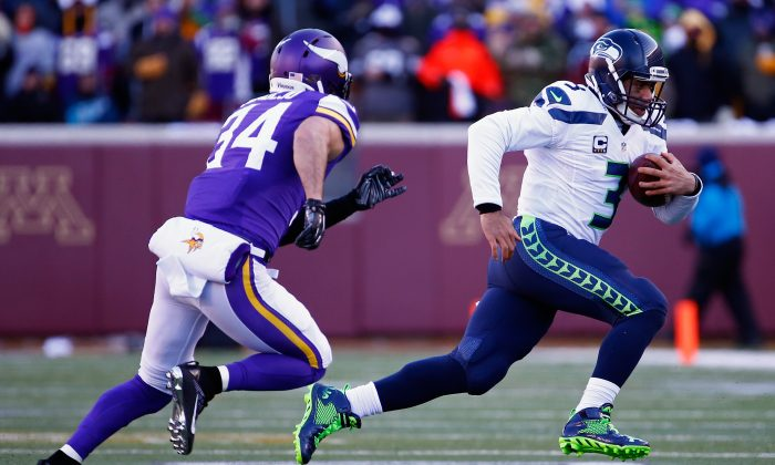 Russell Wilson runs with the ball with Andrew Sendejo in pursuit during the NFC Wild Card Playoff game at TCF Bank Stadium on Jan. 10, 2016 in Minneapolis, Minnesota. (Jamie Squire/Getty Images)