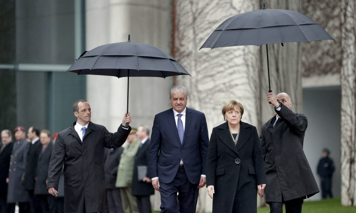 German Chancellor Angela Merkel (R), and the Prime Minister of Algeria Abdelmalek Sellal, attend a military welcome ceremony prior to a meeting at the chancellery in Berlin on Jan. 12. (AP Photo/Michael Sohn)