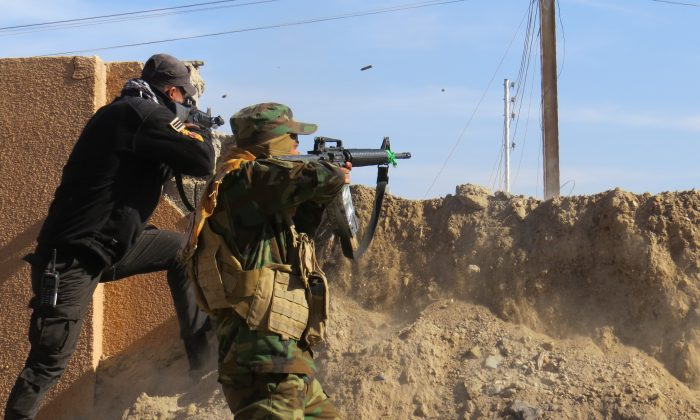 Members of the Iraqi government forces battle with Islamic State (ISIS) fighters east of Ramadi, after they took control of the agricultural area surrounding the eastern part of the capital of Iraq's Anbar Province on Jan. 12, 2016. (Moadh al-Dulaimi/AFP/Getty Images)