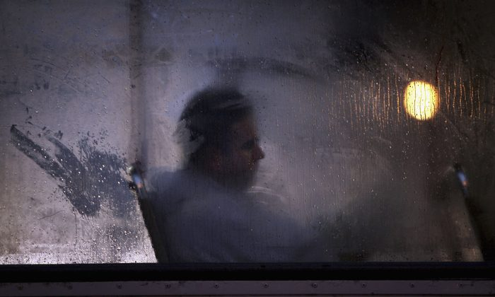 A man makes his way home from work on a bus as darkness falls in Glasgow, Scotland, on Oct. 10, 2005. Seasonal affective disorder (SAD), or winter depression, is a mood disorder related to the change in the seasons and the resulting reduction of exposure to daylight. (Christopher Furlong/Getty Images)