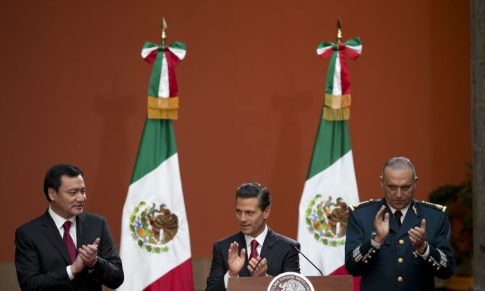"Mexican President Enrique Pena Nieto, flanked by Interior Minister Miguel Angel Osorio Chong, left, and National Defense Secretary Slavador Cienfuegos Zepeda, applauds during a press conference following the capture of fugitive drug lord Joaquin ""El Chapo"" Guzman, in Mexico City, on Jan. 8. (AP Photo/Rebecca Blackwell)"