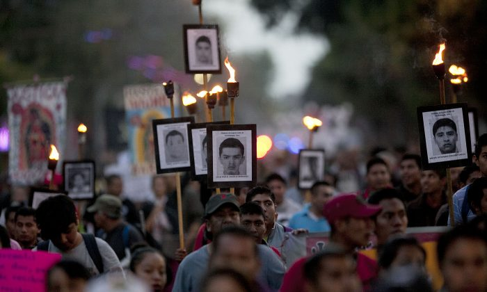 Relatives of the 43 missing students from the Isidro Burgos rural teachers college march holding pictures of their missing loved ones during a protest in Mexico City on Dec. 26, 2015. One year and three months after several students and bystanders were killed and 43 students vanished in the city of Iguala, allegedly taken by police and then handed over to a criminal gang who burned their bodies in a garbage dump, according to a federal investigation. Families of the missing and independent investigators cast doubts on the official version. (AP Photo/Marco Ugarte)