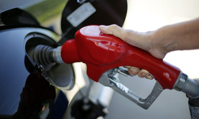 A woman fills her car at a Costco gas station in Robinson Township, Pa., on July 16, 2015. The price of oil continues to fall, extending a slide that has already gone further and lasted longer than most thought, and probing depths not seen since 2003. (AP Photo/Gene J. Puskar)