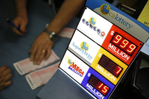 People buy lottery tickets at the Primm Valley Casino Resorts Lotto Store just inside the California border, near Primm, Nev., on Jan. 12, 2016. The Powerball jackpot has grown to over $1 billion dollars for the next drawing on Wednesday. (AP Photo/John Locher)