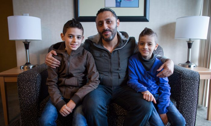 Newly arrived Syrian refugees Ahmad Hwichan and his sons Louai and Qusai pose for a photograph at a hotel where they're living temporarily in Vancouver on Jan. 12, 2016. (THE CANADIAN PRESS/Darryl Dyck)