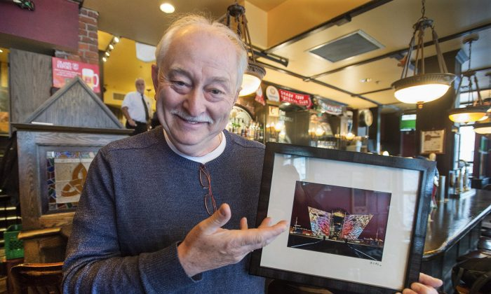Brian Doherty, co-owner of the Old Triangle Irish Alehouse, holds up the framed print that was swiped from the pub on Jan. 6, 2016. The owners and staff decided to use their widely followed social media platforms to recover the picture rather than involve the police. (THE CANADIAN PRESS/Andrew Vaughan)