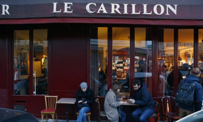 Customers take a drink on the terrace of the Carillon cafe during the re-opening exactly two months after the November attacks, in Paris, Wednesday, Jan. 13, 2016. With the blood and bullets now swept away, the Carillon cafe has reopened its doors for the first time since it was among the Paris sites targeted by Islamic extremists in November. (AP Photo/Francois Mori)
