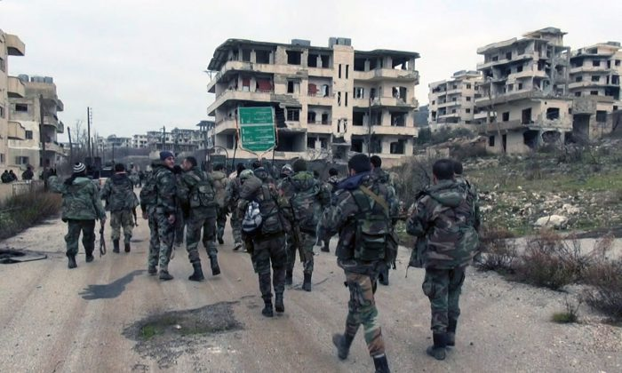 In this photo released on Tuesday, Jan 12, 2016, by the Syrian official news agency SANA, shows Syrian government troops and allied militiamen walk inside the key town of Salma in Latakia province, Syria. (SANA via AP)