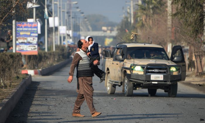 TOPSHOT - An Afghan man kisses his daughter as he walks near an attack from a building close to the Pakistan consulate in Jalalabad on January 13, 2016.  A suicide bombing followed by gunfire rocked an area near the Pakistani consulate in the eastern Afghan city of Jalalabad on January 13, killing at least two police officers, officials said.    AFP PHOTO / Noorullah Shirzada / AFP / Noorullah Shirzada        (Photo credit should read NOORULLAH SHIRZADA/AFP/Getty Images)