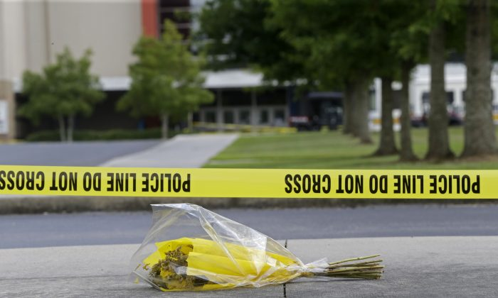 """A bouquet of flowers lies net crime scene tape in the parking lot outside The Grand 16 movie theater in Lafayette, La., Sunday, July 26, 2015, Sunday, July 26, 2015, in Lafayette, La.   John Russell Houser stood up about 20 minutes into Thursday night's showing of """"Trainwreck"""" and fired on the audience with a semi-automatic handgun. (AP Photo/Gerald Herbert)"""