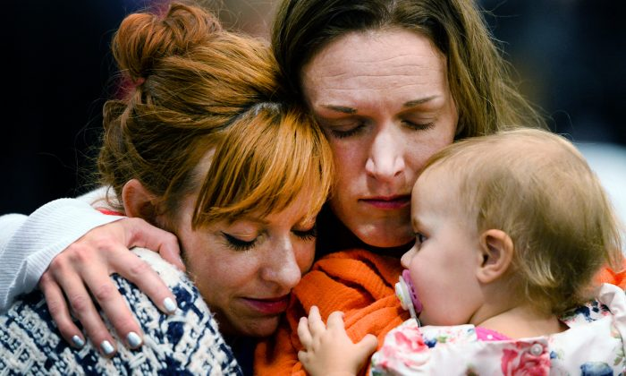 FILE - In this Dec. 19, 2015, file photo, Renee Wetzel, widow of Michael Wetzel, center, and her daughter Allie, are comforted by a woman during the memorial service for her husband at Calvary Chapel Conference Center in Twin Peaks, Calif. Wetzel the widow of Michael Wetzel, killed in last month's mass shooting in San Bernardino has filed four claims with the county and is seeking damages totaling $58 million, according to a newspaper report. (Rachel Luna/The Sun via AP, Pool, File)