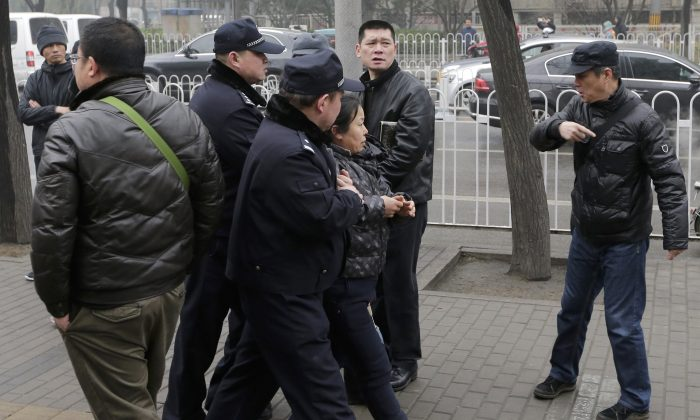Police officers take away a supporter of rights lawyer Pu Zhiqiang near the Beijing Second Intermediate People's Court during Pu's trial in Beijing, Monday, Dec. 14, 2015. (AP Photo/Andy Wong)