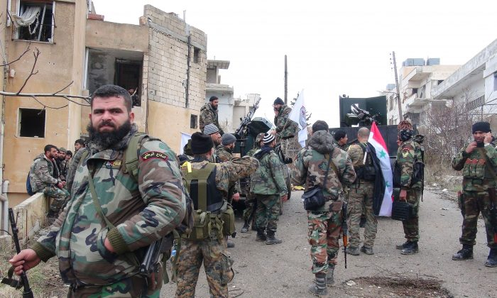 Forces loyal to the Syrian regime stand on a street with national flags after Syria's army and allied forces took full control from rebel groups of the strategic town of Salma, in the northwestern province of Latakia on Jan. 12. (Stringer/AFP/Getty Images)