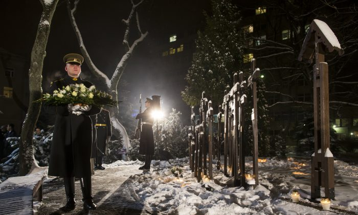 """Lithuanian Army solders take part in a wreath laying ceremony on the eve of the 25th anniversary of the Day of the Defenders of Freedom """"Battle for the Freedom of Nations"""" in Vilnius, Lithuania, Tuesday, Jan. 12, 2016. (AP Photo/Mindaugas Kulbis)"""