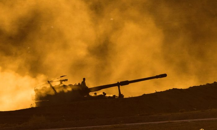 Turkish military mobile artillery unit driving at sunset on a hill overlooking the Syrian city of Kobani, outside Suruc, on the Turkey-Syria border, on Nov. 11, 2014. (AP Photo/Vadim Ghirda)