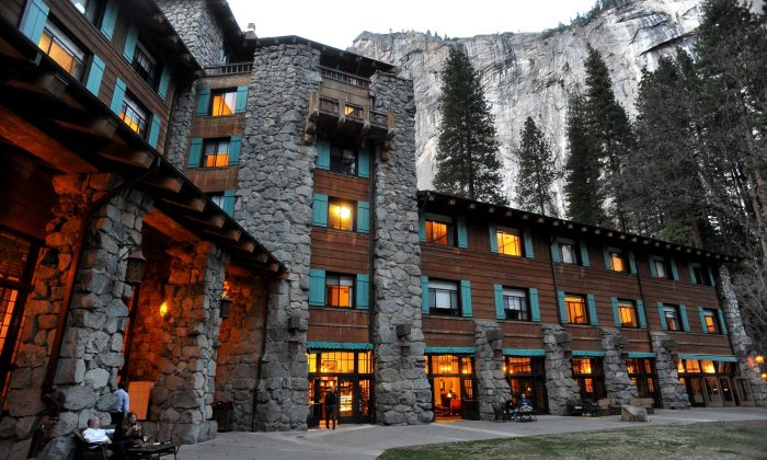 In this March 24, 2014 file photo, the historic Ahwahnee Hotel is lit up as dusk falls over Yosemite Valley, in Yosemite, Calif. The names of iconic hotels and other facilities in the world-famous Yosemite National Park will soon change in an ongoing battle over who owns the intellectual property, park officials said Thursday, Jan. 14, 2016. The famed Ahwahnee Hotel will become the Majestic Yosemite Hotel, and Curry Village will become Half Dome Village, said park spokesman Scott Gediman. (John Walker/Fresno Bee via AP)