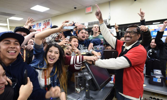 7-Eleven store clerk M. Faroqui celebrates with customers after learning the store sold a winning Powerball ticket on Wednesday, Jan. 13, 2016 in Chino Hills, Calif. One winning ticket was sold at the store located in suburban Los Angeles said Alex Traverso, a spokesman for California lottery. The identity of the winner is not yet known. (Will Lester/The Sun via AP)