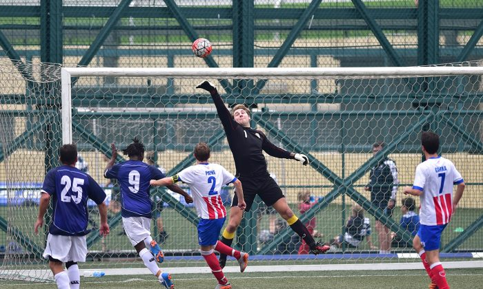 Squadron's goalie covers this goal attempt by Albion during Albion's 3-nil victory in the Yau Yee League, first division match at Sports Road on Sunday Jan 10, 2016. (Bill Cox/Epoch Times)