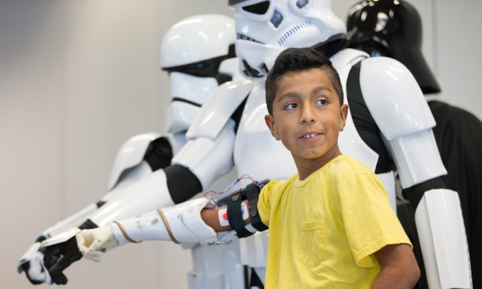 In this Thursday, Jan. 14, 2016, photo, Alvin Garcia Flores poses for photos with Storm Troopers as he shows off his new bionic arm in Omaha, Neb. Garcia Flores, a 4th-grade student at Gateway Elementary School in Omaha, received a 3D-printed bionic arm from Limbitless Solutions, which was delivered by volunteers from the 501st Legion, the national fan organization for Star Wars. (Matt Miller/The World-Herald via AP)