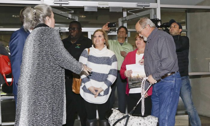 John Robinson, front right, arrives at the Tennessee Lottery headquarters with his wife, Lisa; daughter, Tiffany, center; and family dog Friday, Jan. 15, 2016, in Nashville, Tenn. At left is Rebecca Hargrove, president and CEO of the Tennessee Lottery. The Robinsons claim to have one of the winning tickets in the record $1.6 billion jackpot drawing that took place Wednesday. (AP Photo/Mark Humphrey)