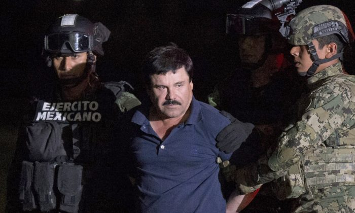 """Mexican drug lord Joaquin """"El Chapo"""" Guzman is escorted by army soldiers  to a waiting helicopter, at a federal hangar in Mexico City, Friday, Jan. 8, 2016. (AP Photo/Rebecca Blackwell)"""