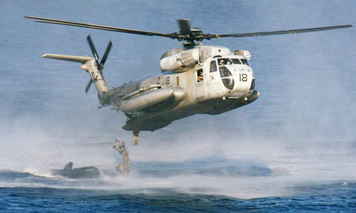 U.S. Marines and their Philippine counterparts jump from a U.S. Marines CH-53D Sea Stallion helicopter at Ternate in Cavite province south of Manila on Feb. 18, 2003. The U.S. Coast Guard says two similar Marine helicopters have collided off the Hawaiian island of Oahu on Jan. 15, 2016. (AP Photo/Bullit Marquez)