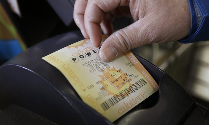 A store clerk removes a Powerball quick pick lottery ticket Wednesday, Jan. 13, 2016, in Oakland, Calif. (AP Photo/Ben Margot)