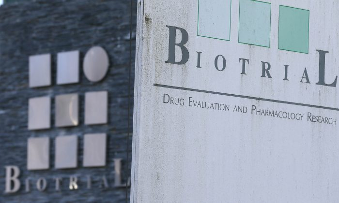 A logo of the Biotrial laboratory is displayed on its building in Rennes, western France, Friday, Jan. 15, 2016.  Officials say six volunteers have fallen ill after participating in a clinical trial in the French city of Rennes and one of them is brain-dead. The French Health Ministry said on Friday that the six were hospitalized after taking a medication that was in the first phase of testing to study safe usage, tolerance and other measures on healthy volunteers. (AP Photo/David Vincent)