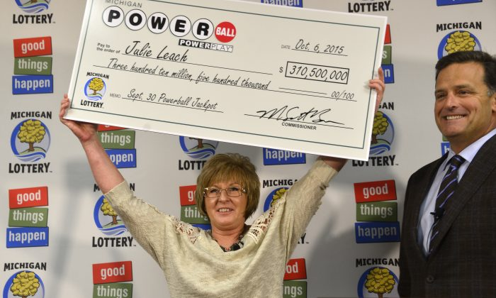 In this Oct. 6, 2015 file photo, Julie Leach of of Three Rivers, Mich., holds her $310 Million Powerball jackpot check, accompanied by Michigan Lottery Commissioner M. Scott Bowen in Lansing, Mich. (Dale G. Young/The Detroit News via AP)