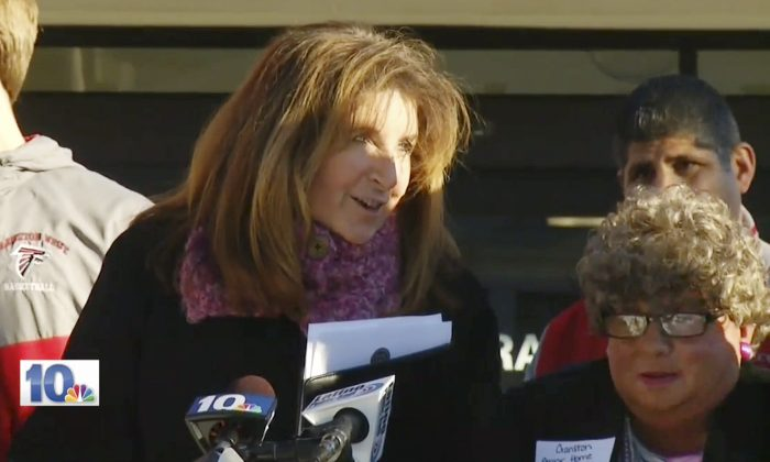 """In this Jan. 5, 2016 still image from WJAR-TV video, Sue Stenhouse, left, executive director of the Senior Enrichment Center, speaks alongside a man dressed as an elderly woman, right, during a news conference in Cranston, R.I., to promote a program for school children to help senior citizens shovel snow during the winter. The middle-aged male bus driver wore a wig, earrings, lipstick and a dress, and a tag that read, """"Cranston Senior Home Resident."""" Stenhouse resigned her position after the incident. (WJAR-TV via AP)"""