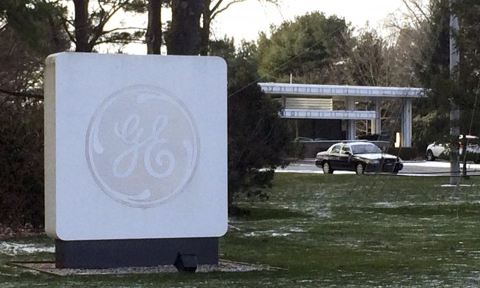 In this Jan. 14, 2016 file photo, the GE logo adorns a sign on the General Electric Co., corporate headquarters campus in Fairfield, Conn. (AP Photo/Michael Melia, File)